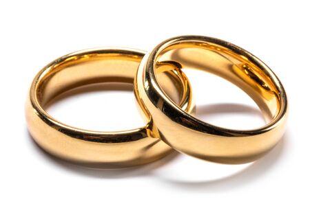 Coppia di anelli di nozze d'oro isolati su sfondo bianco