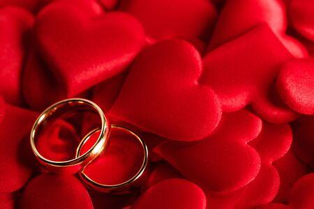 Zwei goldene Eheringe auf rotem Satinherzhintergrund Standard-Bild