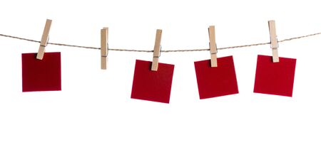 Set of four red blank paper notes held on a string with clothespins isolated on white background Reklamní fotografie