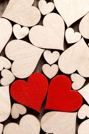 Many wooden colorless hearts background, two red special ones true love concept Stock Photo