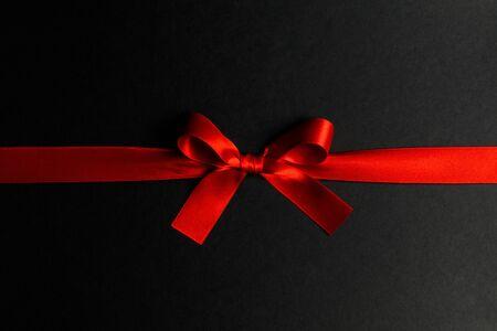 Red satin ribbon bow on black paper background Zdjęcie Seryjne