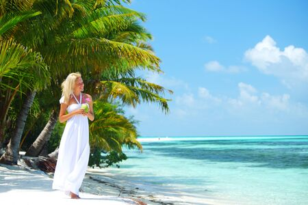 Woman in long white dress walking on tropical beach with palm trees holding coconut cocktail and smiling