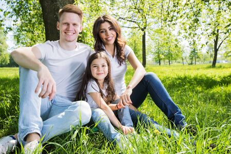 Family of three sitting on spring park meadow grass being happy 版權商用圖片