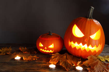 Halloween pumpkin head lanterns burning candles and dry maple leaves on wooden background