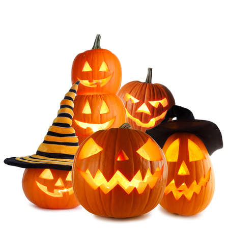 Heap of Jack O Lantern Halloween pumpkins with various different designs and witches hat isolated on white background