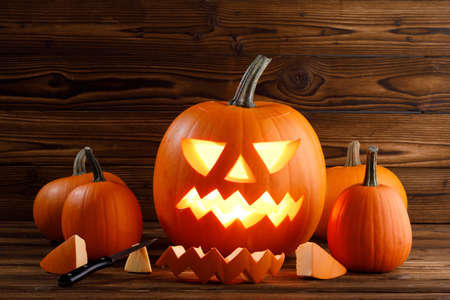 Carving of Halloween pumpkins in progress, pieces and cutting knife on wooden background, lantern is glowing