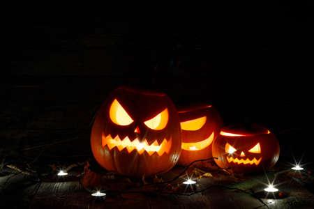 Halloween pumpkin head lanterns and burning candles on black background