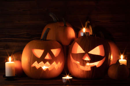 Halloween pumpkin head lanterns and burning candles on wooden background Imagens