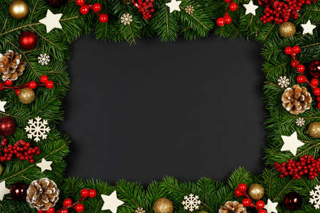 Christmas Border frame of tree branches on black background with copy space, red and wooden decor, berries, stars, cones
