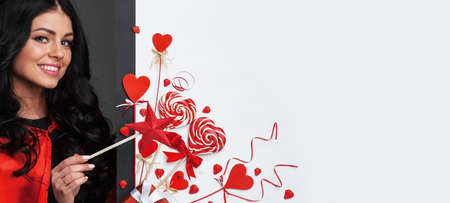 Woman with magic wand near Valentines day decoration and heart shaped lollipops isolated on white background Foto de archivo