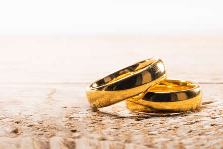 Two golden wedding rings on wooden background with copy space for text