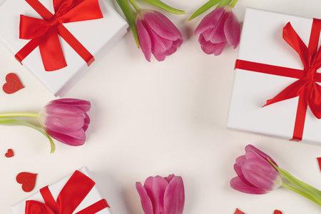 粉红色的郁金香花礼物和红色的心组成在白色的背景顶视图与复制空间。情人节,生日,婚礼,母亲节的概念。本空间