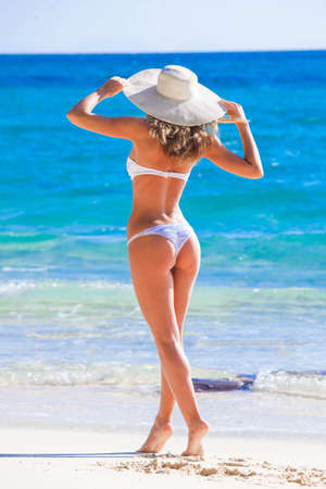 Woman in sunhat and bikini standing on ocean beach on hot summer day