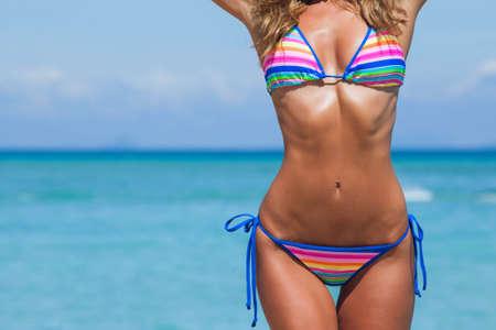 Tanned woman body in bikini, blue sea water in background Archivio Fotografico