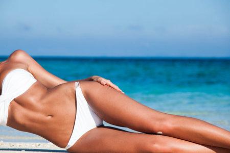 Tanned woman body in white bikini laying in beach, blue sea water in background