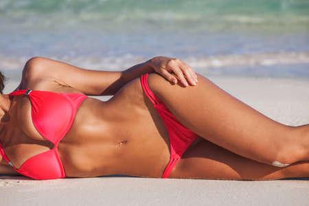 Tanned woman in red bikini laying in beach, blue sea water in background