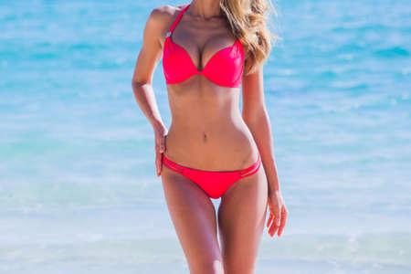 Woman with perfect body in bikini over tropical sea background summer vacation concept Archivio Fotografico