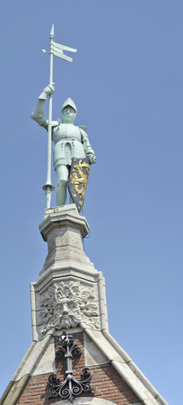 Knight with shining armor standing proud with pylon and shield on top of a building photo