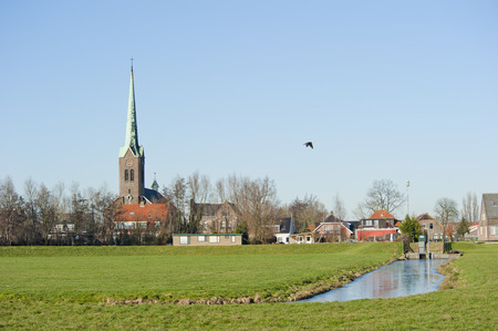 Traditional Dutch small town scenery behind an water embankment at Hoogmade, Netherlands photo