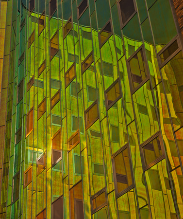 Office building with green, yellow  and orange reflexions in windows