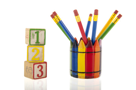 A collage of colourfull pencils in a cup next to three 1-2-3 cubes isolated over a white background photo