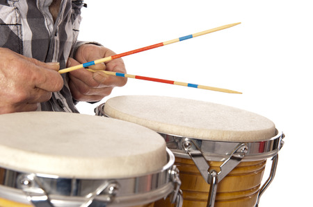 drumming: Male figure playing and drumming on bongo set on his lap and with drum sticks