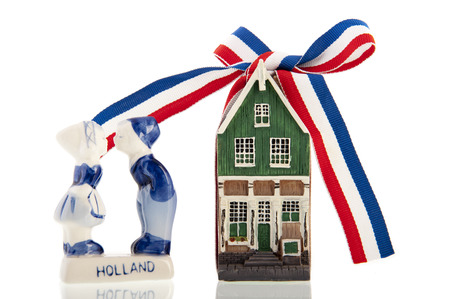 Old Dutch canal house with a red-white-blue ribbon knotted in a bow next to kissing old Dutch farm kids, all isolated over a white  photo