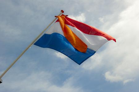 Nederlandse vlag, rood, wit en blauw met de oranje wimpel van de Koninklijke Koninkrijk bij de inauguratie dag van koning Willem-Alexander op april 30, 2013
