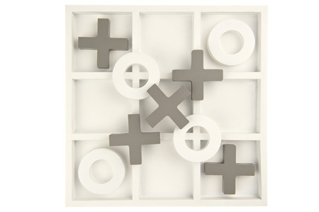 Wooden noughts and crosses game board in gray and white colors and playing stones decorated and isolated in white  photo