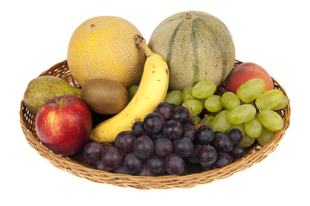 Large fruit basket with banana, apple, nectarine, peach, kiwi, pear, melons, green and blue grapes photo