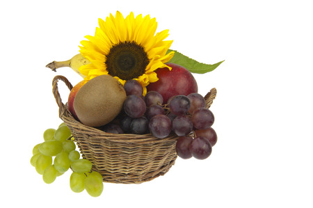 Basket with banana, apple, nectarine, kiwi, green and blue grapes decorated with sunflower photo