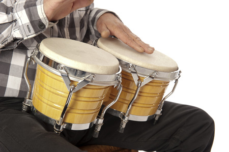 drumming: Male figure playing and drumming on yellow bongo on his lap