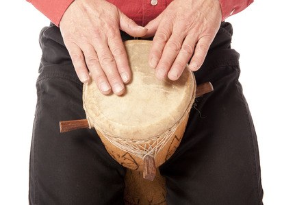 drumming: Male figure playing and drumming on African drum on his lap Stock Photo