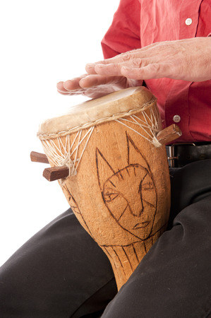 Man playing and drumming on African drum on his lap photo