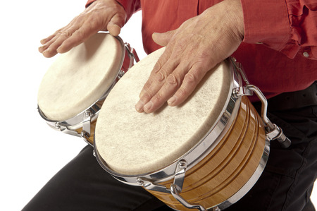 Male figure playing and drumming on bongo set on his lap photo