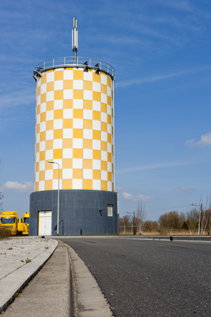 watermanagement: Modern yellow white checkered water tower against a blue sky at Alphen aan den Rijn, the Netherlands, on april 7, 2013