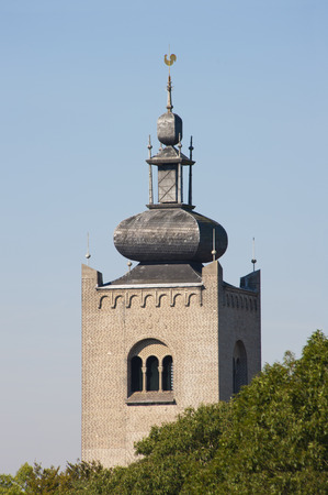 Historic tower of the monastery of the Order of the Holy Cross at Amersfoort, the Netherlands behind surrounding tree tops on september 6, 2010 photo