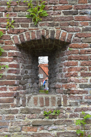 embrasure: Embrasure in the ancient city defence wall of Amersfoort with the Duth flag in the background