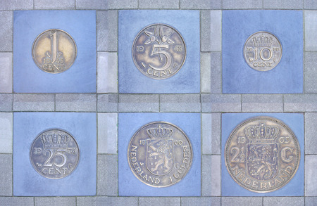 five cents: Collection of former Dutch coins cemented in sidewalk, fit in a frame              Stock Photo