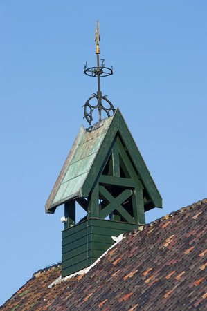 Quadrangular green wooden belfry with weathercock and wind-flower of the Catholic Church at Hoogmade, the Netherlands on january 28, 2011 photo