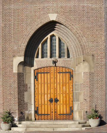 recess: Wooden entrance door with decorative fittings in arch chaped wall recess of the Catholic Church at Hoogmade, the Netherlands on january 28, 2011 Stock Photo