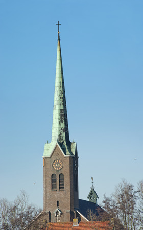 Historic tall slim green Church tower with clock and cross at Hoogmade, the Netherlands on january 28, 2011 photo