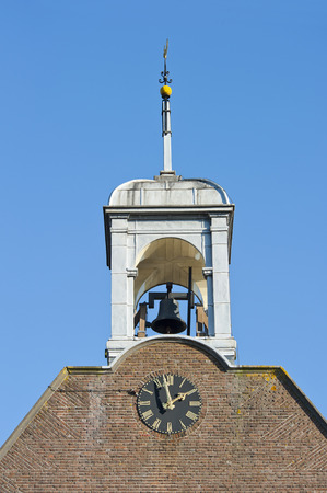 Quadrangular white wooden belfry with weathercock bell and clock of the Protestant Church at Hoogmade, the Netherlands on january 28, 2011 photo