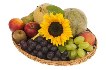 Basket with banana, apple, nectarine, peach, kiwi, pear, melons, green and blue grapes decorated with sunflower photo