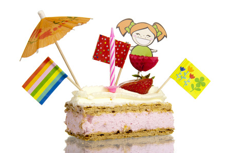 Pastry treat with sweet glaze and whipped cream topping filled with creamy strawberry filling, decorated with candles, flags, umbrellas and puppets isolated on white background photo