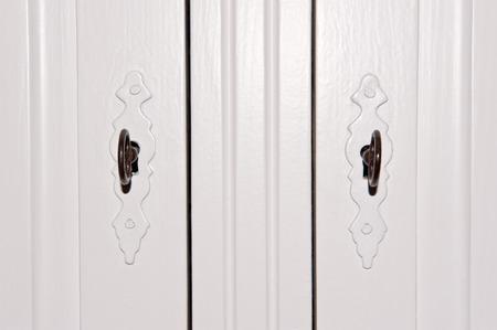 closet door: Closeup of white closet locks with vintage door fittings and black iron keys Stock Photo