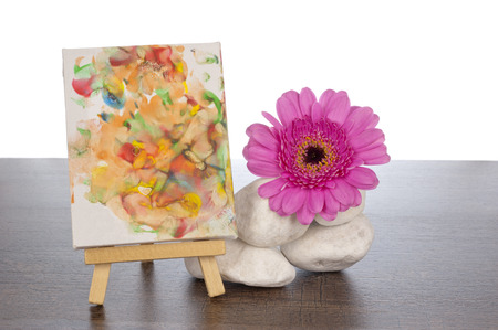 Pile of white rocks on a dark brown wooden shelf decorated with a pink gerbera and a painting on an easel photo