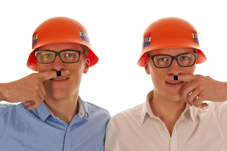 Two men with orange party German war helmets and Hitler moustaches drawn on fingers photo