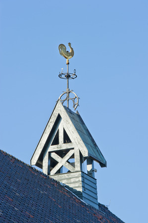 Quadrangular white wooden belfry with weathercock and wind-flower of the blue roof photo
