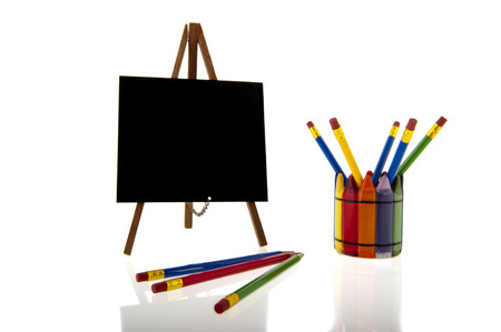 A blackboard on a tripod easel next to a collage of colourfull pencils in a cup isolated over a white background photo